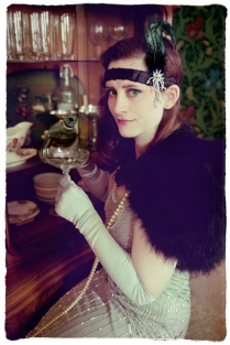 Girl in 1920s dress with vintage cocktail glasses and cabinet